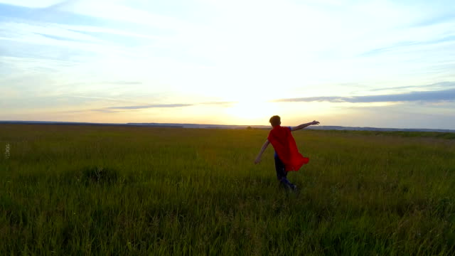 A boy in a superman costume runs across the green field at sunset video