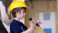 Boy in builder helmet sitting in excavator video