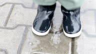 Boy in rubber boots leaps over a puddle video
