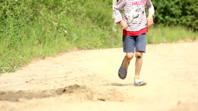 boy in sneakers runs on the road, hurt knee video