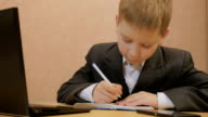 Boy in suit using a laptop, writing a note and thumb up video