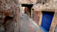 A boy in the age of twelve passing by with as bicycle on a narrow pedestrian street in Essouira video