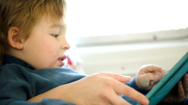 Boy in the train using touchpad held by mother video