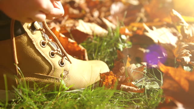 Boy is lacing up his boots on a beautiful autumn afternoon video