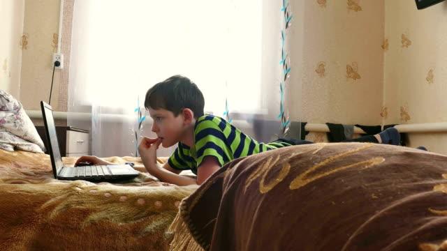 boy is playing laptop internet browsing video