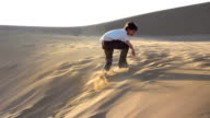 Boy jumping and rolling down sanddune, late afternoon video
