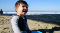 Boy Laughs While Throwing Sand video