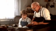 HD DOLLY: Boy Learning How To Make Shoes video