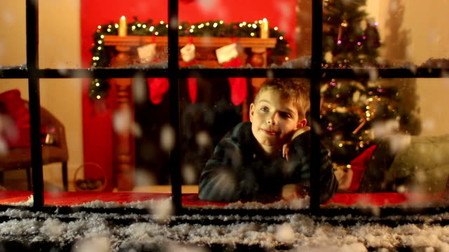 Boy looking at snow through window - Christmas video