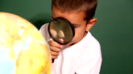 Boy looking through magnifying glass at globe video
