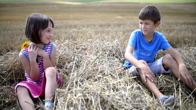 boy makes a gift flower to a girl, sitting on hay, slow motion video