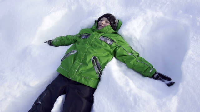 Boy makes snow angels in the winter video