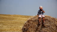 boy on a haystack in a field of hay throws up, farmer boy in the village video