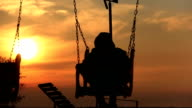 Boy on a swing at sunrise a boy on a swing at sunset, silhouette, river video