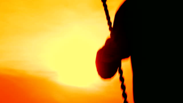 boy on a swing at sunset video