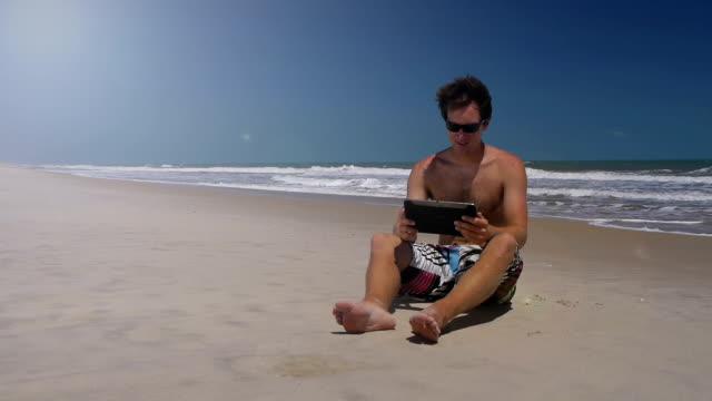 Boy on beach using digital tablet, girl joins him video