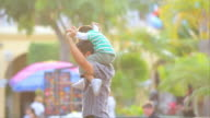 Boy on dad's shoulders in city video