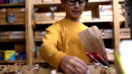 Boy packed products of plastic in a paper bag video