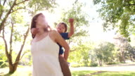 Boy piggybacking on his mother's back in a sunny park video