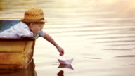 Boy places a paper boat on the water's surface and blows for it to sail away video