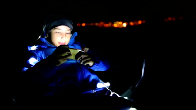 Boy playing a video game outdoors at night video