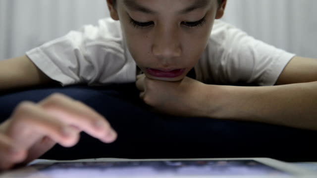 Boy playing digital tablet video