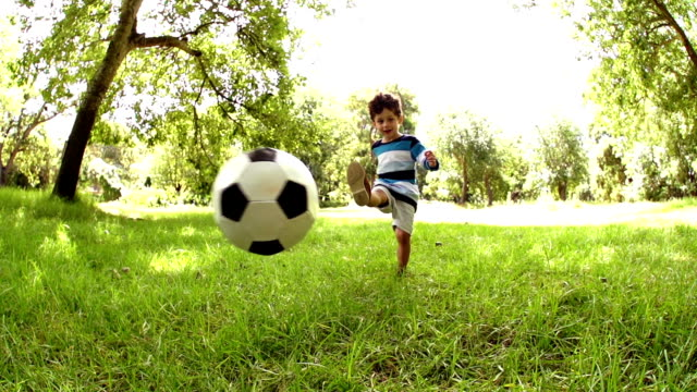 Boy playing football in park video