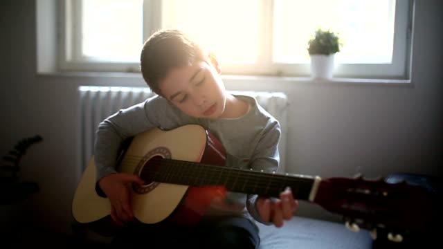 Boy playing guitar at home video