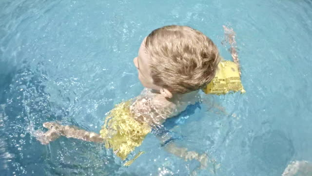 Boy playing in swimming pool video