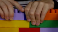 boy playing in the colored blocks sitting at the table video
