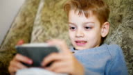 boy playing on a mobile phone video