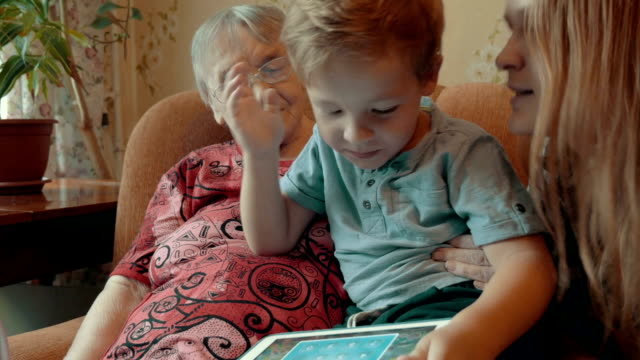 Boy playing on pad with mother and granmother video