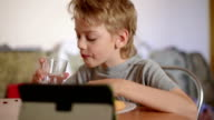 boy playing on the laptop while eating, close up video