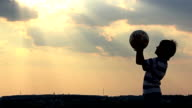 boy playing with a ball in a field at sunset, boy dreams of becoming a soccer player video
