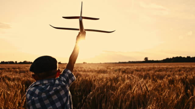 SLO MO Boy playing with airplane in wheat field video