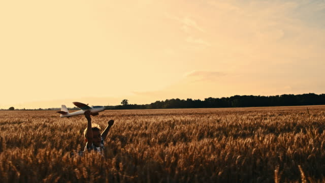 SLO MO Boy playing with airplane toy in wheat field video