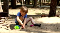 A boy plays in the sandbox video