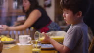 A boy pouring orange juice from a pitcher into a glass, at the table video