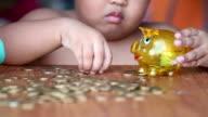 Boy putting money in piggy bank video