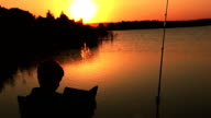 boy reading a book on a fishing trip at sunrise at sunset sun glare on the water video
