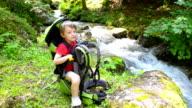 Boy relaxing in a kid carrier near river video