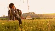 SLO MO Boy relaxing on a tree swing video