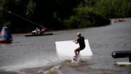 Boy rides on a wakeboard and jumping from a springboard video