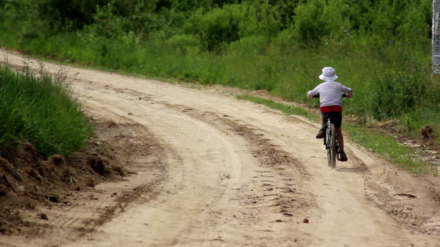 boy riding a bike on rural road in field video
