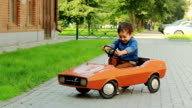 Boy riding a toy car video