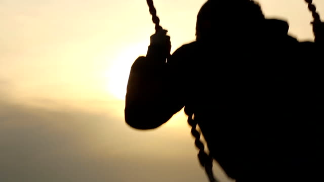 boy riding on a swing at sunset video