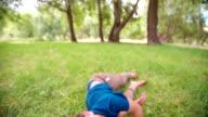 Boy rolling in grass in slow motion video