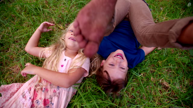 Boy rolling in grass with girl lying next to him video