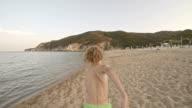 Boy running along sandy beach video