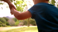 Boy running holding hands with mother in slow motion video